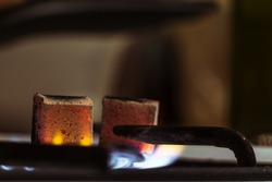 Coconut hookah coals stand on a gas stove and heat up at home or in a hookah bar.