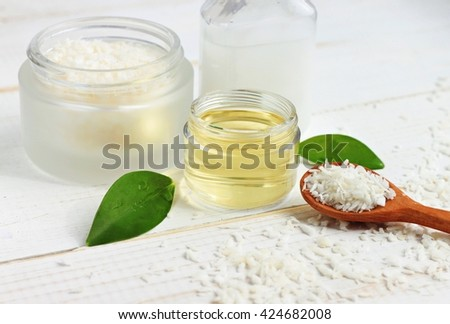 Coconut oil jar, coconut shavings spoon, fresh plant, white table. Natural skincare beneficial products.