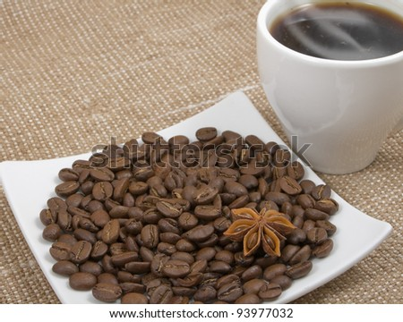 coffee bean and anise lie on a saucer on a background hot coffee and sacking
