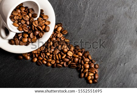 Coffee beans in an upturned white cup