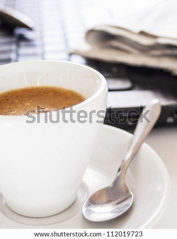 coffee cup with newspaper and laptop