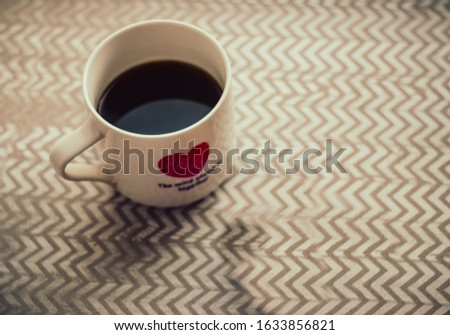 coffee n a mug, a pair of cookies on a table with zigzag ornaments, shot from above Foto stock ©