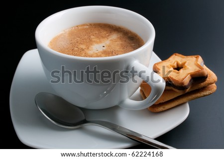 Coffee. White porcelain cup of freshly brewed coffee close-up arranged with two  sandwich-biscuits spoon and plate on dark background