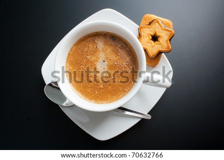 Coffee. White porcelain cup of freshly brewed coffee top view close-up arranged with two sandwich-biscuits, spoon and plate on dark background