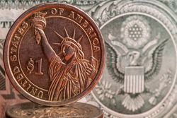 Coin with denomination a one American dollar on the background of a fragment of one American dollar bill