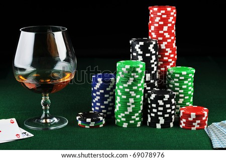 color chips for gambling, drink and playing cards on green