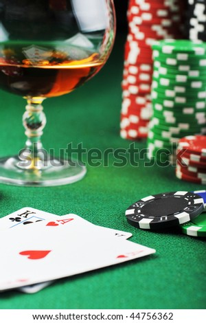 color chips for gamblings, drink and playing cards on green