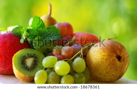 Colored fresh fruits on green background.