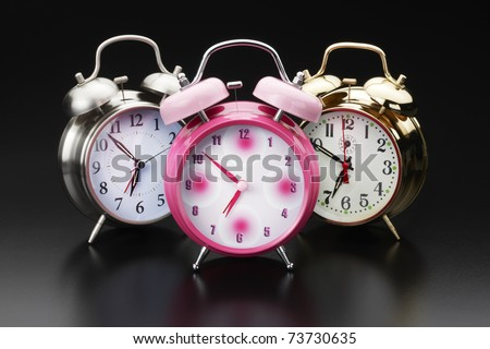 3 colorful, classic alarm clocks shot on reflective surface