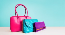 3 colorful fashion bags purses isolated on light blue background.