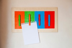 Colorful handmade scrapbook with blank sheet for scrapbook notes, reminder, shopping list and notice. Mural made with wood and clothespin and painted. Diy concept. Reminder concept.