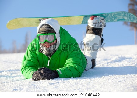 colorful image of young snowboarder in green jacket lying on the snow