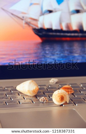colorful seashells lie on a silver computer keyboard against the background of a screen with a picture of the sea