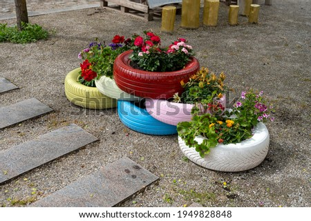 6 colorful tires with flowers in them - shot from an obliquely angle Foto stock ©