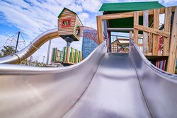 Colorful wooden playground with slide in a kindergarten park for play time outdoor