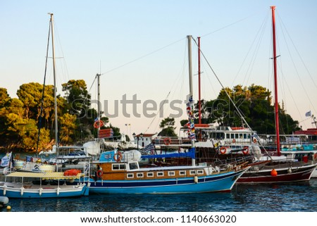 Colorful wooden tourist boats anchored in the beautiful Greek port are waiting for the cheerful tourists for the next day.  #1140663020