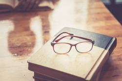 Composition with glasses and book for world philosophy, on wood table, iteracy day concept.