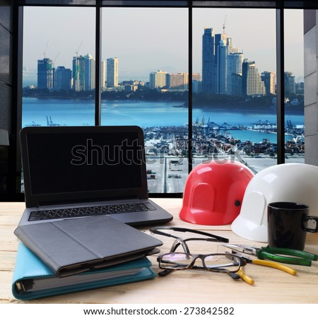 computer and builder\'s work tool on wooden table with cranes at the container port terminal with big city background