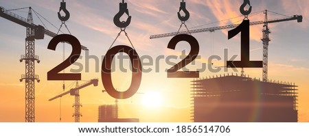 2021 concept. building construction try to complete 2021 new year sign . 2021 happy new year building in sunrise or sunset