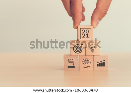 2021 concept business man hand arranging wood block . icon of business strategy including element with goal, idea, leadership, management of time, Knowledge, Initiative, Human relations in 2021 year