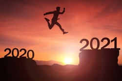 2021 concept, business man jumpinng up from 2020 to 2021 Newyear Silhouette young woman standing and raise hand up to Happy new year  with sunrise, sunset background