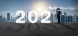 2021 concept, business man on the road of 2021 new year think analysis to use a strategy , vision to develop to make a business model growth with high performance, financial  and predict the economy