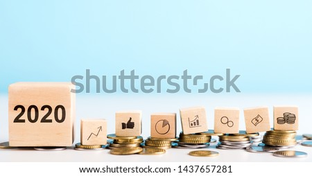 2020 concept. Government economy improvings. Wooden blocks with coins, dollar, graphs laying on real money, panorama, copy space