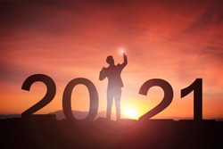 2021 concept, 2021 Newyear Silhouette young business happy mand standing and raise hand up to Happy new year  with sunrise, sunset background