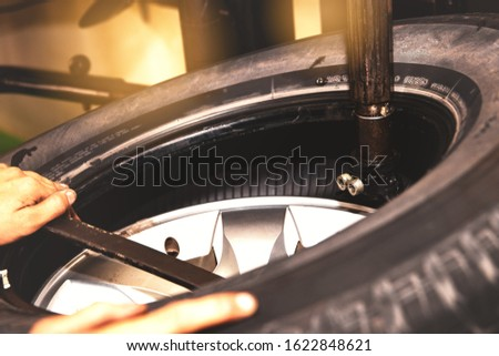 Concept of changing tires for safer driving : Closeup of a professional mechanic, remove tire rims using modern tools in the car service station. Stock fotó ©