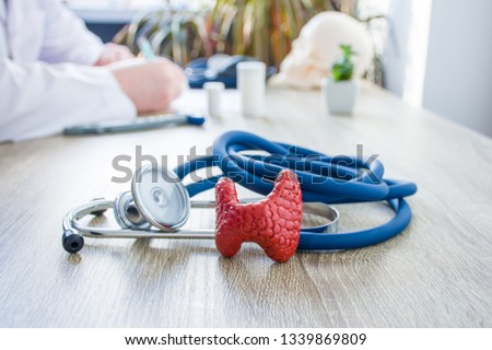 Concept photo of diagnosis and treatment of thyroid. In foreground is model of thyroid gland near stethoscope on table in background blurred silhouette doctor at table, filling medical documentation
