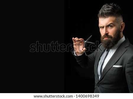 Confident barber at barbershop. Barber and hairdresser salon. Beard care, perfect beard. Bearded man in formal business suit. Brutal male hipster cut hair with hairdressing scissors - copy space.