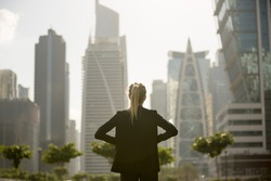 Confident businesswoman standing strong looking at the city high-rises view. Business ambition and aspire.