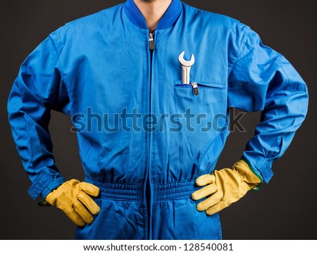 Construction worker with wrench in his pocket against gray background