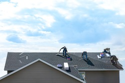 4 construction workers fixing roof against clouds blue sky, install shingles at the top of the house. Renovate, improvement, build home exterior by professional teamwork. Safety and protection concept