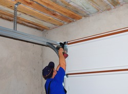 Contractor Installing Garage Door Post Rail and Spring Installation and Garage Ceiling.  Spring Tension Lifts  Metal Section Garage Door Panel that the Motor does not have to Lift Entire Weight.