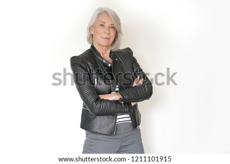 Cool senior woman on isolated white background in leather jacket