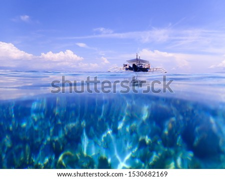Coral reef under water and a pump boat on the sea at Balicasag Island, Bohol, Phillipines #1530682169