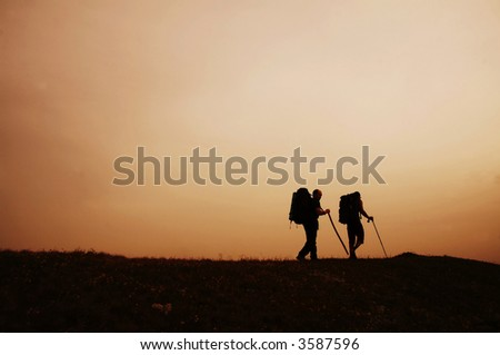 Couple going along hill on sunset - stock photo