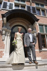 couple posing outside on stairs in front of city hall on wedding day