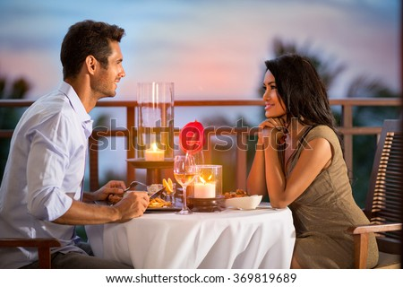 Couple sharing romantic sunset dinner on tropical resort
