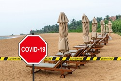 'COVID-19'' road sign and a quarantine warning tape against loungers and folded beach umbrellas in a desolate tropical beach