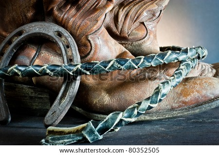 ,Cowboy boots,horseshoe and whip on wood,
