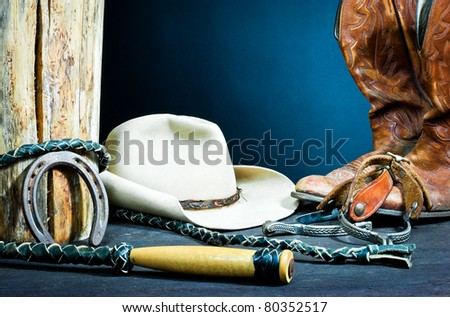 ,Cowboy boots,horseshoe,whip,spurs and hat on wood,