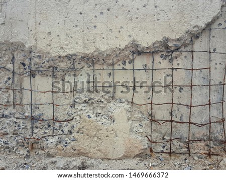 Cracked cement wall,The cement wall that is under construction is broken until the inner steel is seen. #1469666372