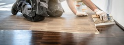 Craftsman oils the freshly sanded parquet floor by applying the oil roughly with a spatula