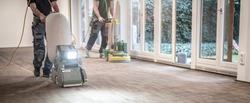 Craftsmen sand a parquet floor