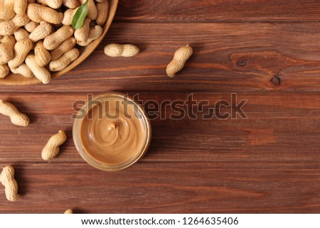 creamy peanut butter in a glass jar and peanuts beans on wooden background top view