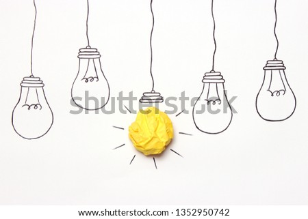 "creative concept ""idea"", a new idea. Painted light bulb with a crumpled paper yellow ball."