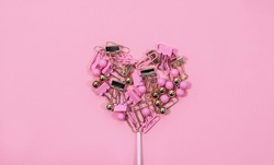 Creative Valentine's day background. Heart lollipop made from colored stationery clips and pins on a pastel pink background. Heart background. Minimal concept, top view.