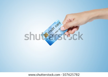 credit card hold on hand over blue background.